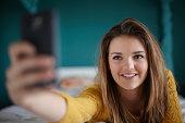 Teenage girl in bedroom taking a selfie