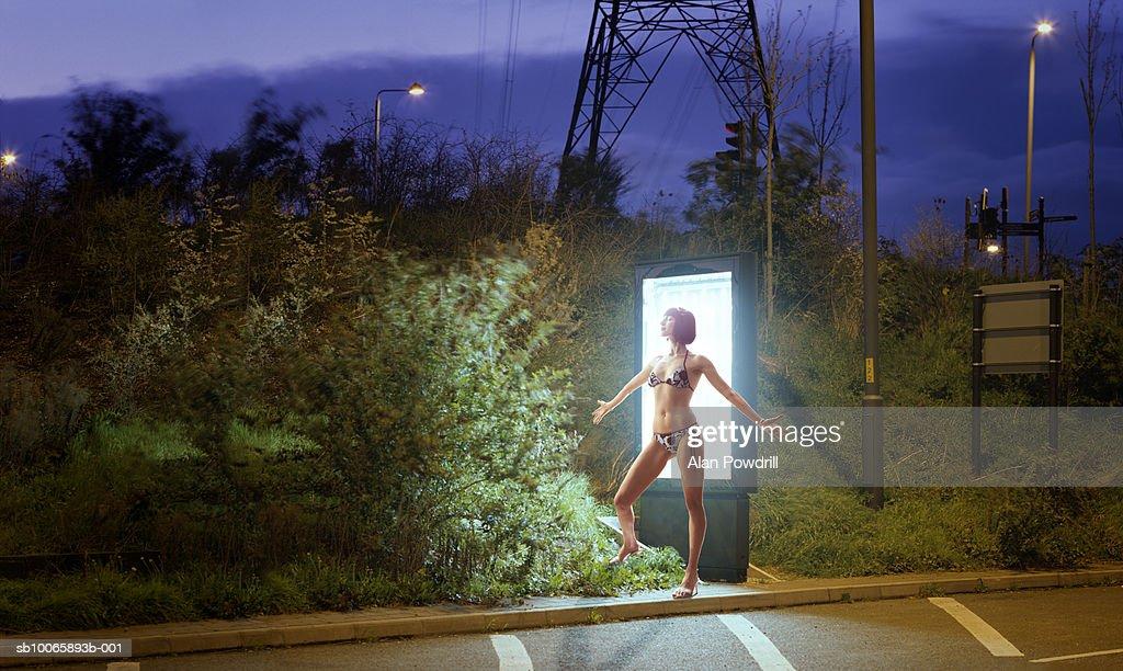 Teenage girl (16-17) in bikini tanning in front of advertising lightbox : Stock Photo