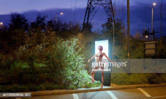 Teenage girl (16-17) in bikini tanning in front of advertising lightbox : Foto de stock