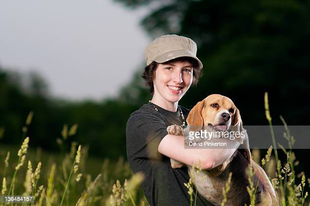Teenage girl in cap and basset hound dog in field