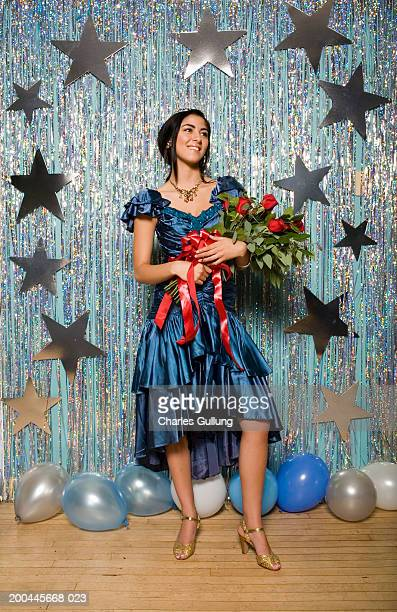 Teenage girl (16-18) in formal dress wearing crown, holding roses
