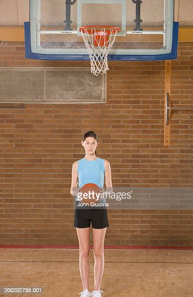 Teenage girl (13-15) in gym holding basketball, portrait