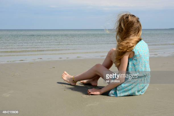 Teenage girl in light blue sundress sitting at the sea