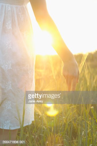Teenage girl (16-18) in long grass, touching grass with hand, close-up : ストックフォト