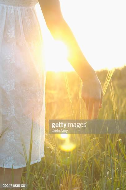 Teenager Mädchen (26) in long grass, berühren Gras mit hand, cl