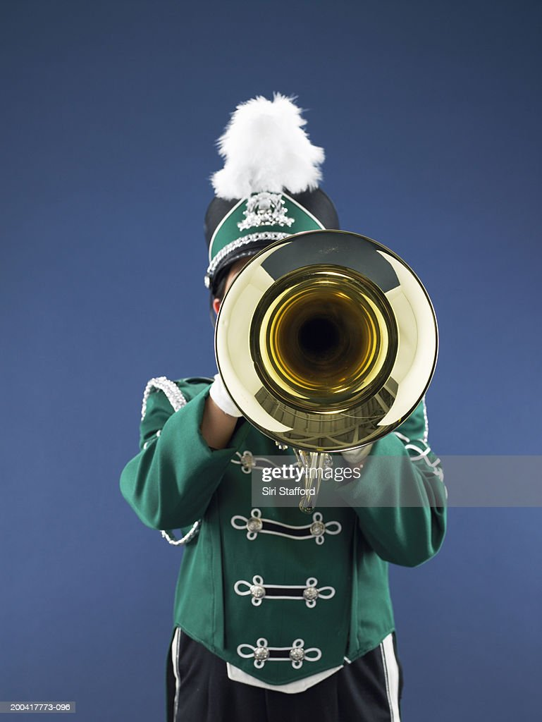 Teenage girl (14-16) in marching band uniform playing horn : Stock Photo