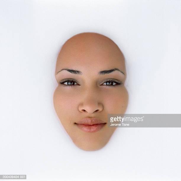 Teenage girl (18-20) in milk bath, overhead view, portrait