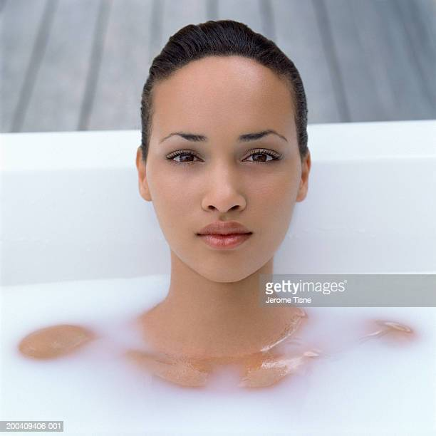 Teenage girl (18-20) in milk bath, portrait