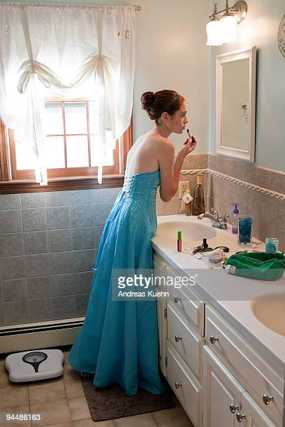 Teenage girl in prom dress putting on lipstick.