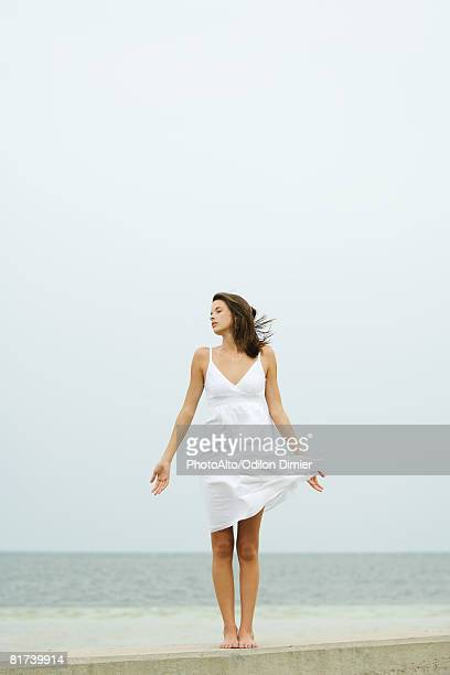 Teenage girl in sundress standing at the beach, tousled by wind, eyes closed