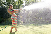Teenage girl in swimsuit and beach towel spraying garden hose outdoors