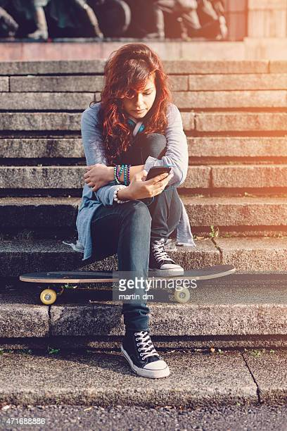 Teenage girl in the city texting on smartphone