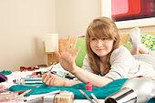 Teenage Girl In Untidy Bedroom Painting Nails