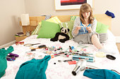 Teenage Girl In Untidy Bedroom Waxing Legs
