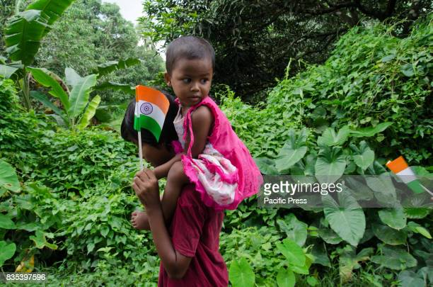 A teenage girl is carrying her sister during the road procession on 71st Independence day in Shivniwas village