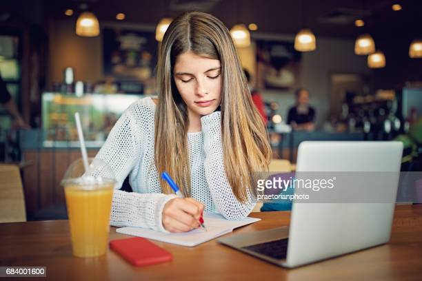 Teenage girl is studying in a college campus cafeteria in her break