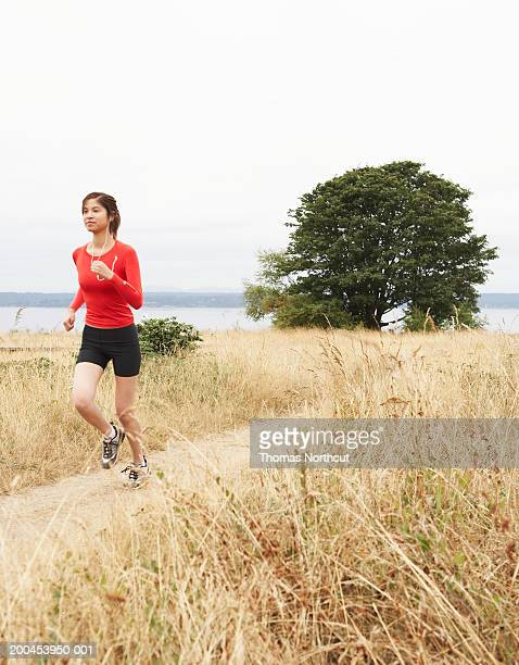 Teenage girl (15-17) jogging and listening to MP3 player in park