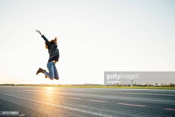 teenage girl jumping high at sunset, lens flare, copy space