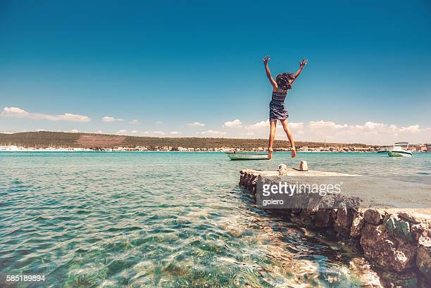 teenage girl jumping high on landing stage at croatian coast