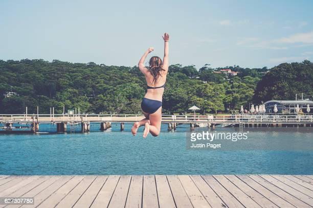 Teenage Girl Jumping into Sea