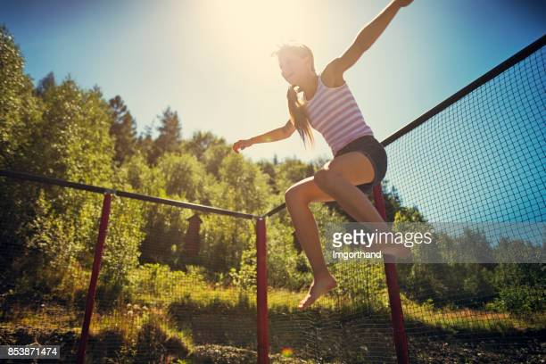 Teenage girl jumping on large trampoline