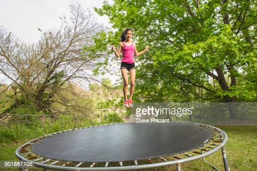 Teenage girl jumping on trampoline, outdoors