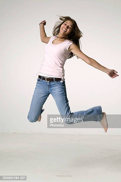 Teenage girl (16-17) jumping, studio shot,