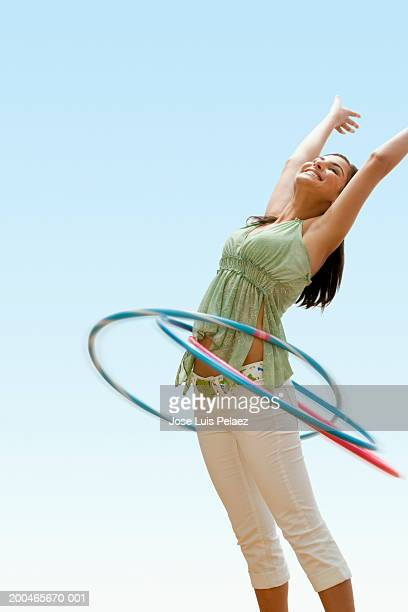 Teenage girl (14-16) jumping, twirling plastic hoops