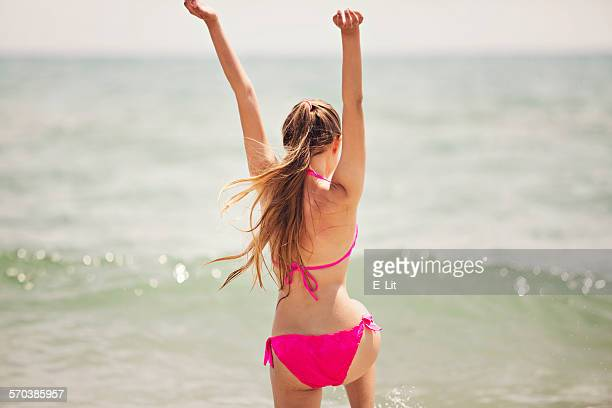 Teenage girl jumping up in the air on the beach