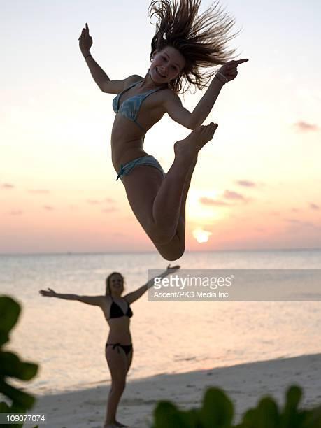 Teenage girl jumps in air above beach, mom below