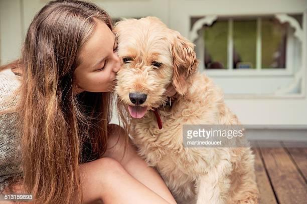 Teenage girl kissing and hugging her Goldendoodle dog on porch.
