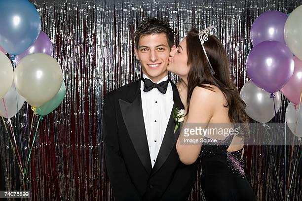 Teenage girl kissing boy on cheek
