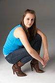 Teenage Girl Kneeling In Studio