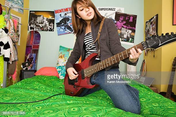 Teenage girl (14-16) kneeling on bed, playing electric guitar