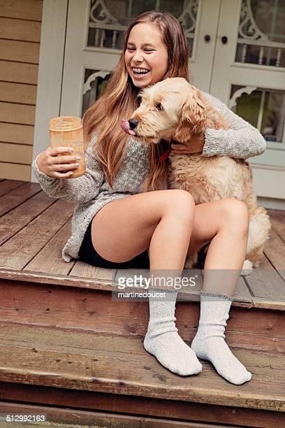 10 代の少女の笑顔、犬とピーナッツバターにポーチ。