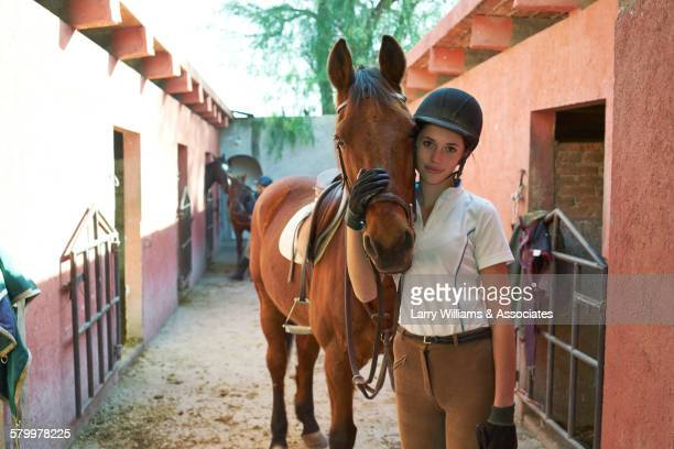 Teenage girl leading horse in stable on ranch