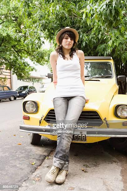 Teenage girl leaning against car