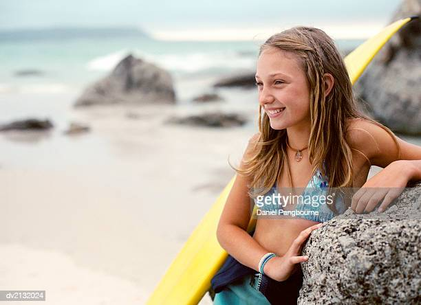 Teenage Girl Leans by a Rock on the Beach With Her Surfboard, Smiling