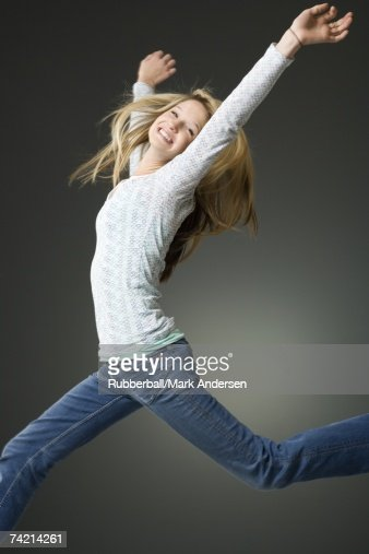 Teenage girl leaping and smiling