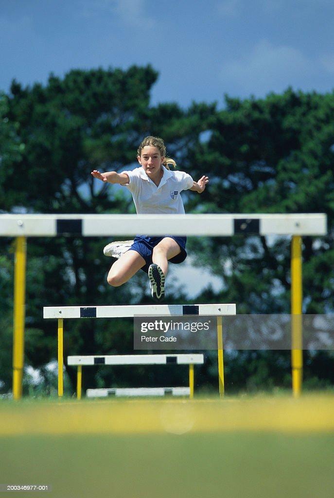 Teenage girl (14-16) leaping hurdles : Stock Photo