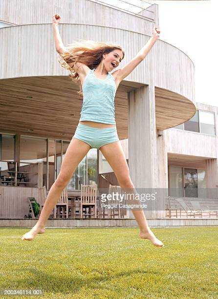 Teenage girl (1-15) leaping on lawn