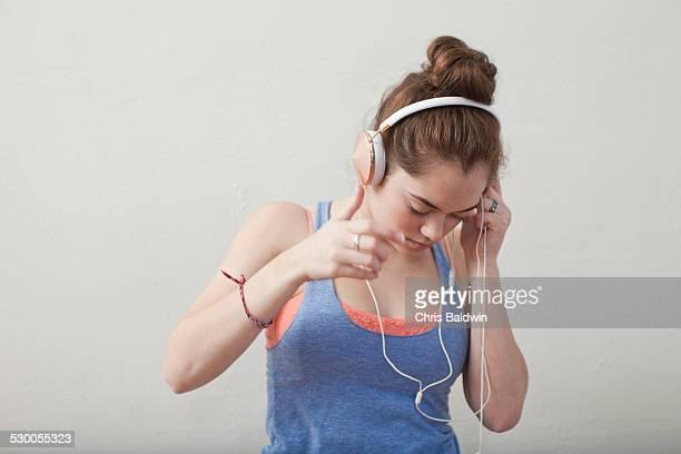 Teenage girl listening to headphones in ballet school