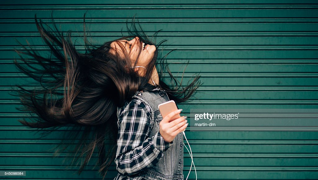 Teenage girl listening to the music and shaking head : Stock Photo