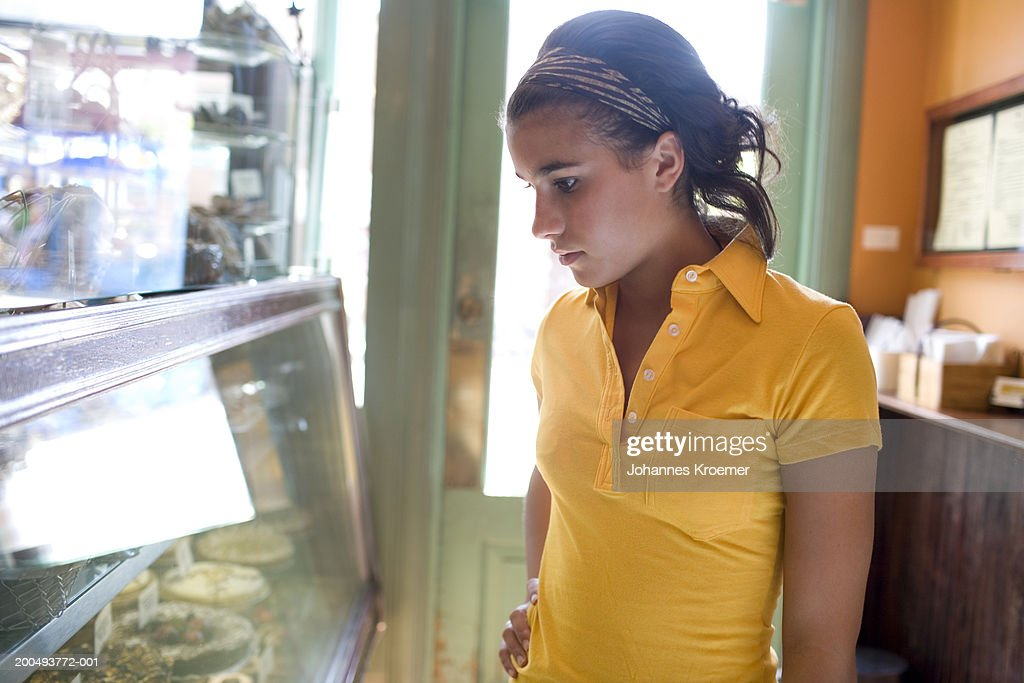 Teenage girl (16-18) looking at food display in cafe, side view : Stock Photo