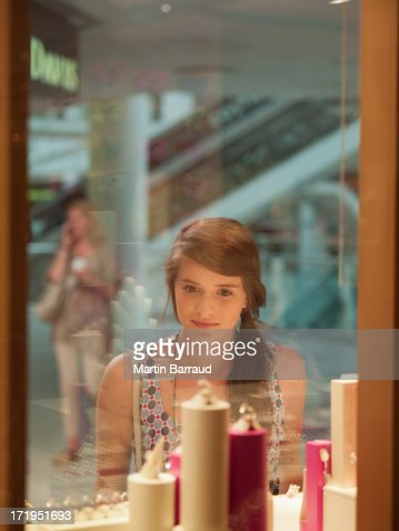 Teenage girl looking at jewelry in display case