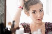 Teenage girl looking at mirror