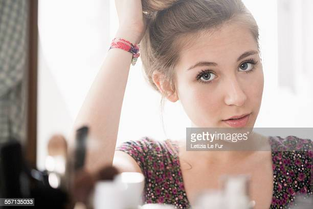 Teenage girl looking at mirror
