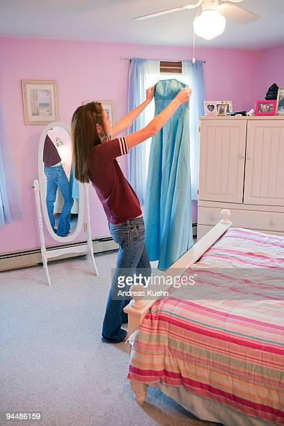 Teenage girl looking at prom dress.