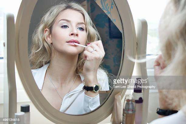 Teenage girl looking in mirror, applying make-up
