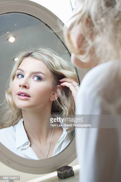 Teenage girl looking in mirror, doing her hair